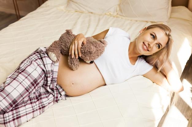 テディベアを自宅でベッドで休んで妊娠中の女性