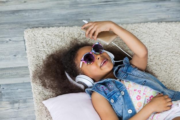 かわいいアフロガール自宅で音楽を聴く