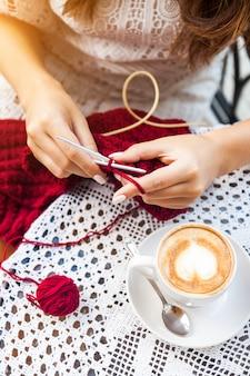Молодая женщина, вязание на террасе в кафе