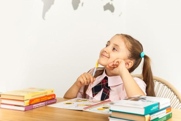 Девушка учится за столом на белом фоне