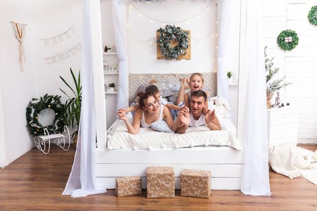 家族はベッドに横たわっています。冬休みのクリスマスと新年のコンセプト