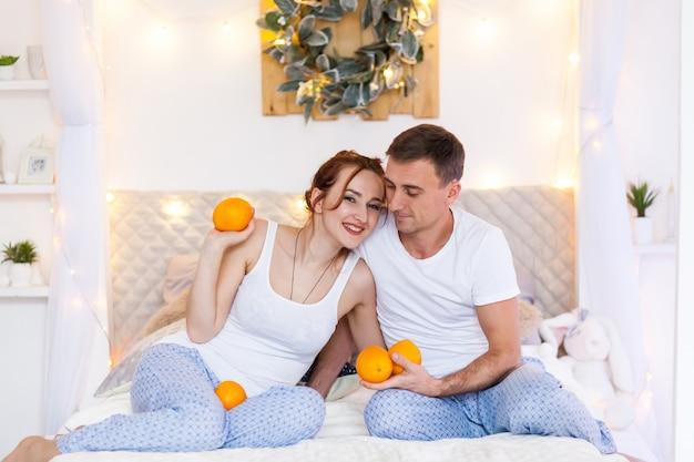 Пара влюбленных в пижамах, лежа на диване. рождественское время. дом отдыха