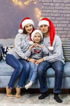 Портрет семьи в красных колпаках санта