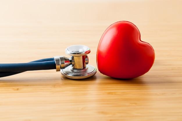 Здравоохранение и медицинская концепция. стетоскоп и красное сердце на деревянном столе.