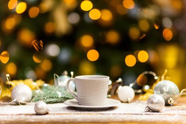 ゴールドの光沢のあるクリスマスデコレーションと白いコーヒーマグカップ。