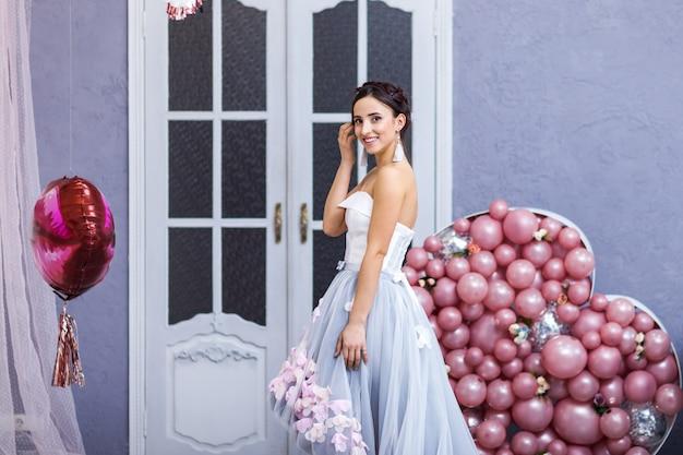 Счастливая женщина в платье из тюля с розовыми баллонами. роскошь