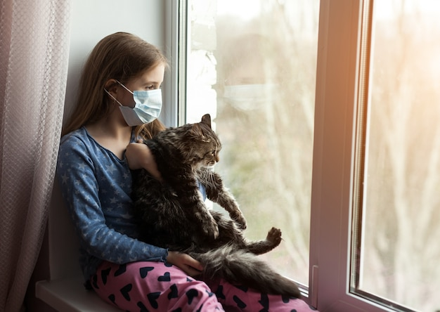 猫を押しながら自宅でアレルギーに苦しんでいる医療マスクの女の子