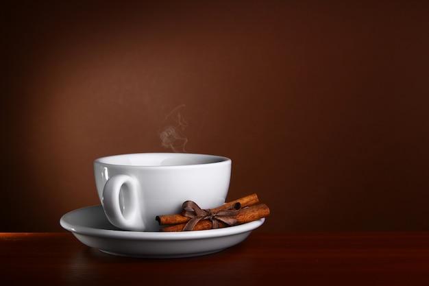 Чашка горячего кофе на коричневом фоне