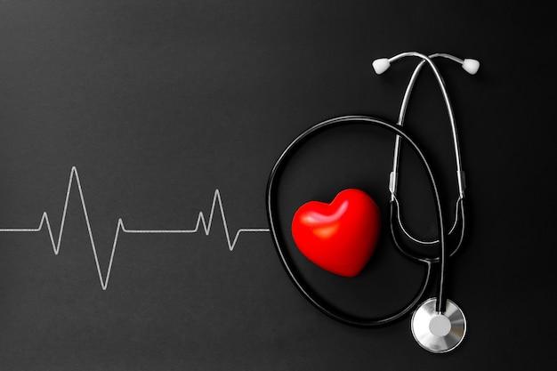 赤いハートと黒い紙に聴診器。医師が病院で治療とケアの患者を使用するためのフラット横たわる不可欠なアイテム。