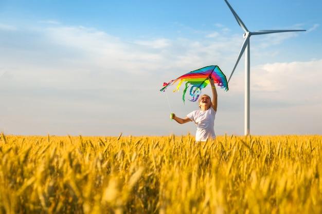 小さな女の子が凧で麦畑を走る