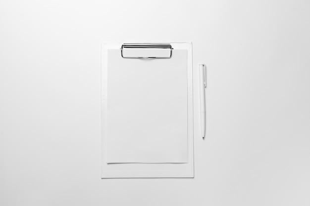 Белый буфер с чистым листом бумаги и ручкой