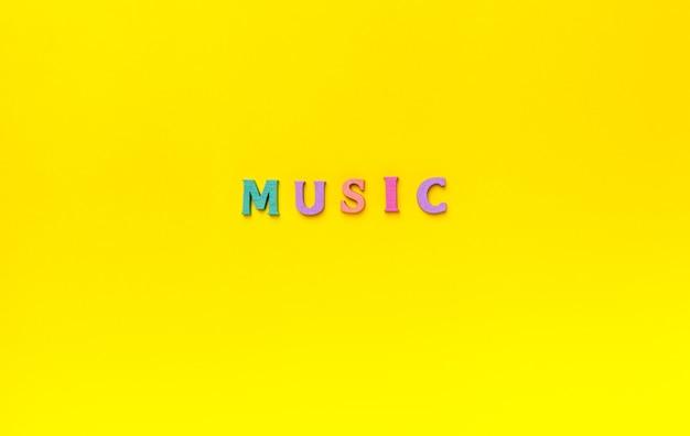 黄色の背景上の音楽のレタリングの単語へのクローズアップ。音楽愛好家のコンセプト