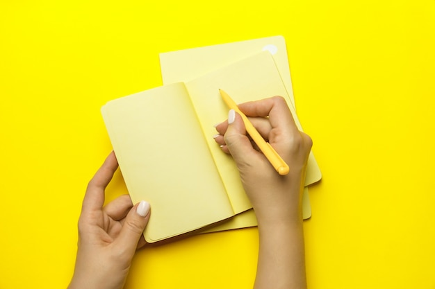 Рука женщины с желтой ручкой и запиской