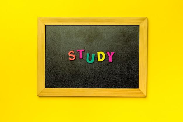 黄色の背景に木製黒板の単語を研究します。
