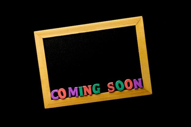 Бизнес-концепция - доска с надписью скоро на черном столе.