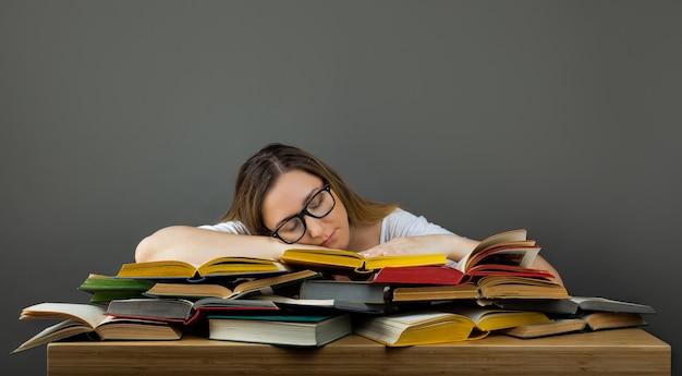 Уставший студент в очках спит на книгах в библиотеке