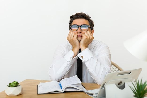 仕事の概念に飽きて、疲れたやる気のない男性労働者が職場で時間を無駄にしている