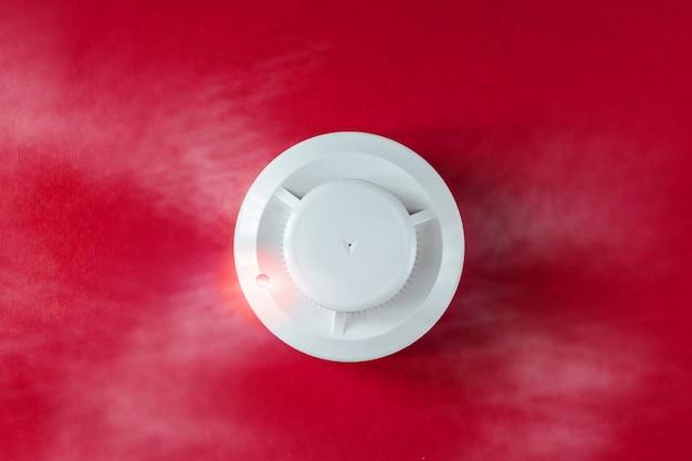 煙探知機と赤い背景の上の火災探知機