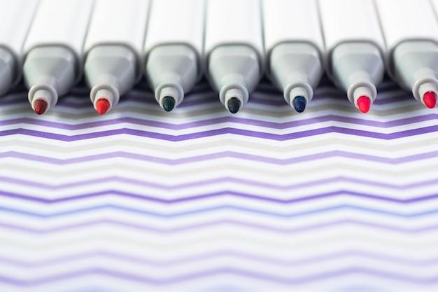 白い波状の背景に分離された色マーカーペン。