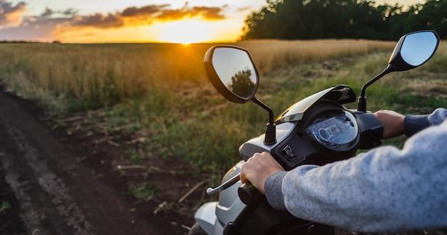 夕焼け空に対して森の中の空の道に沿って乗る