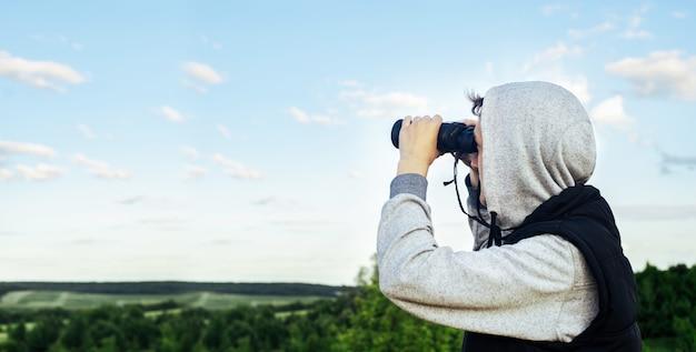 空と緑の丘に対して現代の双眼鏡を持つ男。狩猟、旅行、野外レクリエーションの概念。