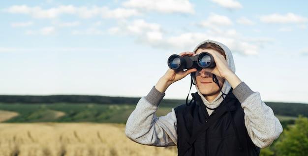 Человек с современным биноклем против неба и зеленых холмов. концепция охоты, путешествий и отдыха на природе.