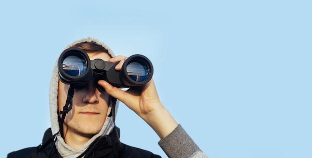 空と緑の丘に対して現代の双眼鏡を持つ男。狩猟、旅行、野外レクリエーションの概念。コピースペースをバナーします。