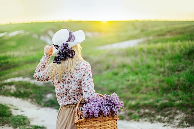 帽子とドレスの花のバスケットを持つ若い女の子金髪