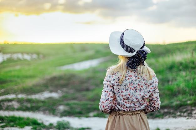 帽子をかぶった金髪の少女と丘の間の歴史的な衣装が道の上に立っています。