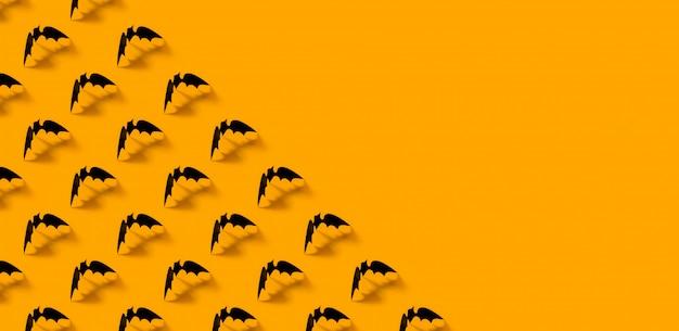 オレンジ色の落ちる影とミニマルな黒い紙バットパターン。