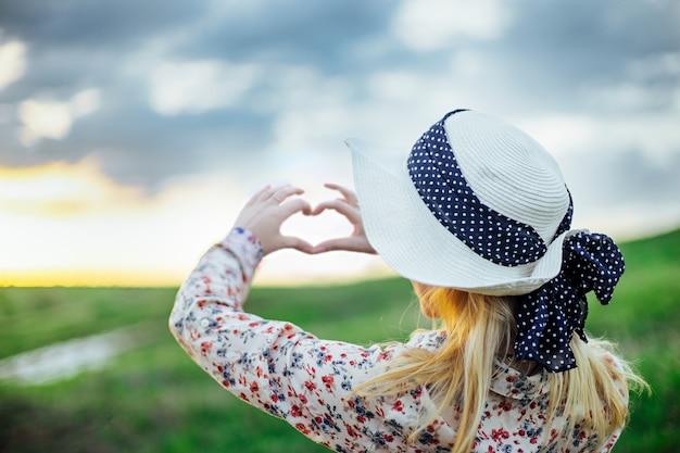Маленькая девочка в шляпе делая символ сердца с ее руками на заходе солнца.