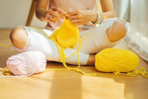 かぎ針編みの女性。少女は座って編み糸から編みます。