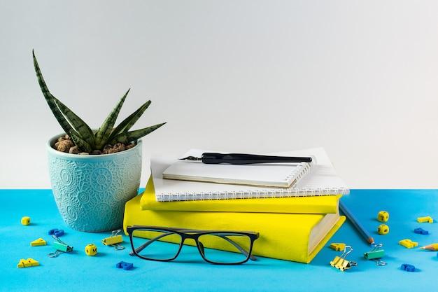 メガネ教師の本;木製の手紙とテーブルの上の多肉植物のポット。青い紙の背景に。先生の日のコンセプト。コピースペース。