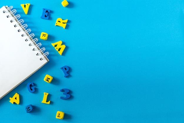 青色の背景に学用品。学校と教師の日の概念。コピースペースを持つテーブルの上の木製の手紙。