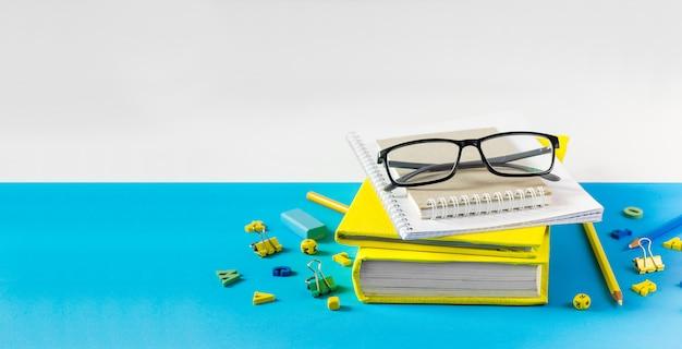 先生のメガネ、本、青いテーブルの上の木製の手紙。学校と教師の日の概念。コピースペース。