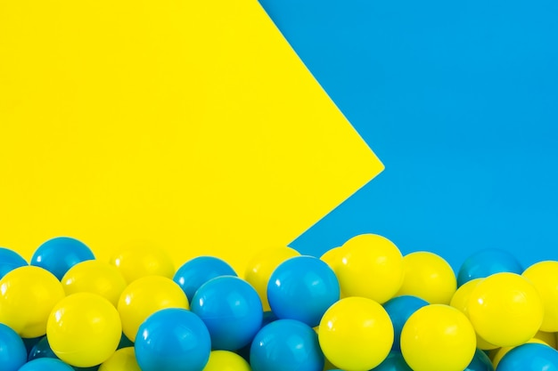 ゲームルームのプールで黄色と青のプラスチックボール