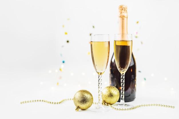 Сверкная предпосылка нового года с шампанским, бутылкой и украшениями. рождество и концепция счастливого нового года.