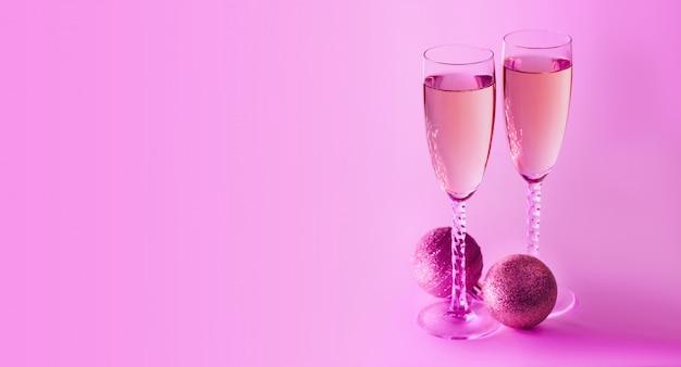 シャンパンとピンクのネオンの背景に輝く新年。クリスマスと新年あけましておめでとうございますコンセプト。コピースペース。