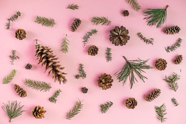 Рождественская композиция. хвойные ветви деревьев и огонь конуса на розовый. рождество, зима. плоская планировка, вид сверху