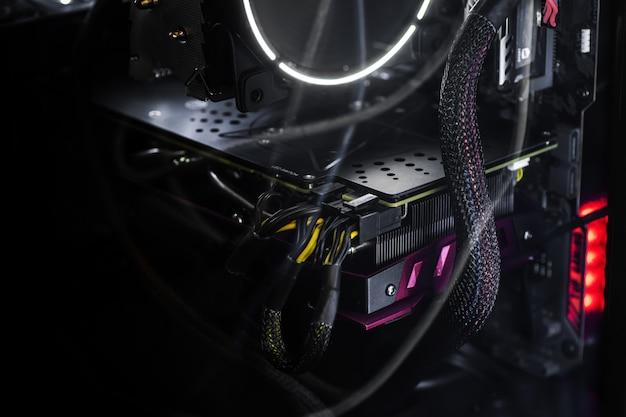 コンピューター内部の黒い壁にバックライト付きのクローズアップビデオカード。コンピューターゲーム、サイバースポーツ、コンピューターの修理の概念。バナー形式、壁紙。