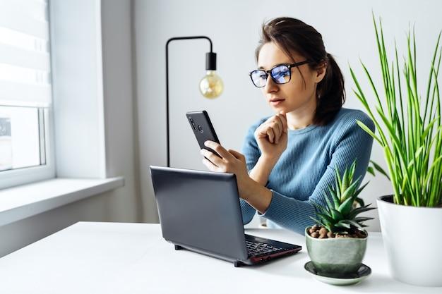 Молодая женщина в очках работает в домашнем офисе успешным менеджером или фрилансером на работе. дистанционное обучение. онлайн покупки, домашняя работа, внештатный и онлайн концепция обучения.