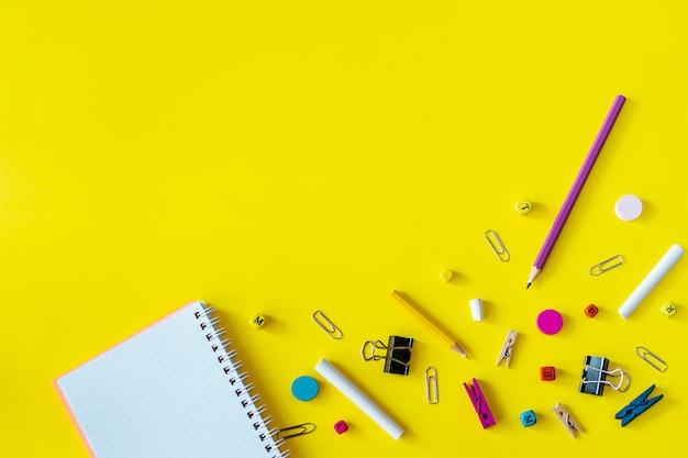 コピースペースと黄色の背景に色とりどりの学用品
