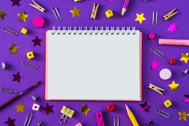 Разноцветные школьные принадлежности на фиолетовый фон с копией пространства.