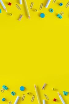 色とりどりの学用品は、コピースペースと黄色の背景に提供します。ソーシャルメディアストーリーのための垂直フラットレイ