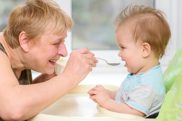 祖母はスプーンから離乳食を与えます