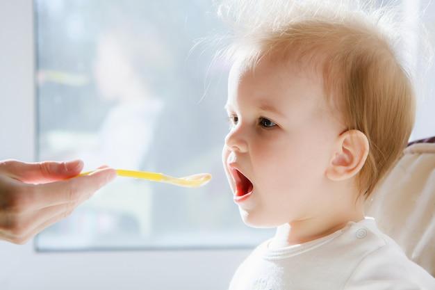 Матери кормят ребенка творогом