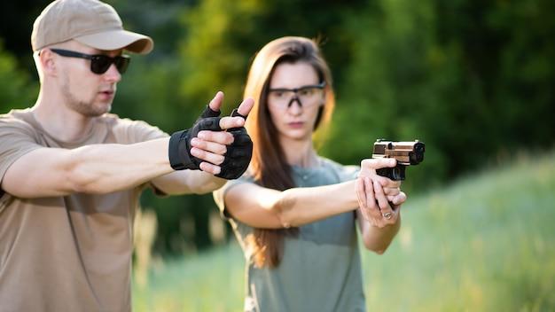 Инструктор учит девушку стрелять из пистолета на полигоне