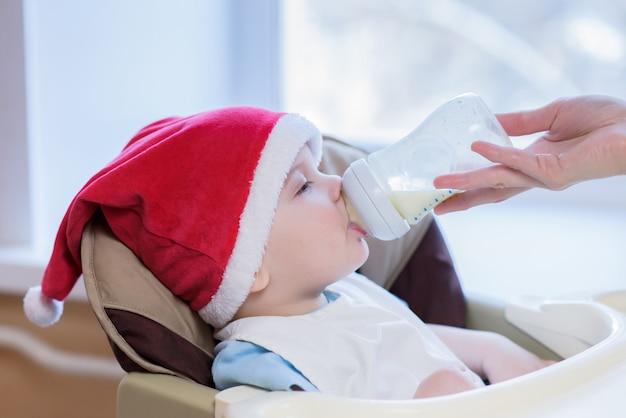 お母さんは新年の帽子をかぶった赤ちゃんに餌をやる