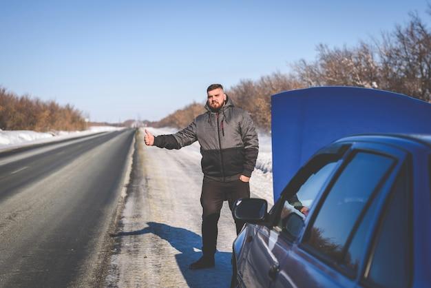 Парень ловит машину, стоящую у дороги
