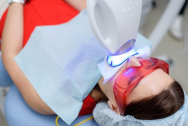 Пациент проходит процедуру отбеливания зубов ультрафиолетовой лампой.